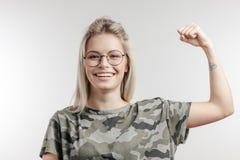 Η χαμογελώντας νέα γυναίκα τυφλώνει μέσα τους δικέφαλους μυς κάμψης μπλουζών χρωμάτων, εξετάζοντας τη κάμερα στοκ φωτογραφίες