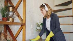 Η χαμογελώντας νέα κυρία καθαρίζει τον πίνακα με το υγρό ύφασμα που κάνει τα οικιακά και που ακούει τη μουσική μέσω των ακουστικώ φιλμ μικρού μήκους