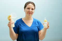 Η χαμογελώντας νοσοκόμα κρατά την αντλία στηθών, μπουκάλι του γάλακτος μικτή σίτιση, που συντηρεί τη γαλακτοπαραγωγή της εργασίας Στοκ φωτογραφίες με δικαίωμα ελεύθερης χρήσης