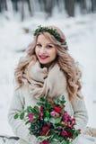 Η χαμογελώντας νύφη της σλαβικής εμφάνισης με ένα στεφάνι των wildflowers κρατά ένα χειμερινό υπόβαθρο ανθοδεσμών γαμήλιος χειμών Στοκ φωτογραφία με δικαίωμα ελεύθερης χρήσης
