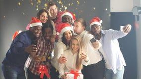 Η χαμογελώντας ομάδα φίλων γιορτάζει το γεγονός βραδιού με Selfie στη γιορτή Χριστουγέννων φιλμ μικρού μήκους