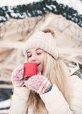Η χαμογελώντας όμορφη νέα γυναίκα πίνει ένα καυτό κακάο υπαίθριο στοκ εικόνες