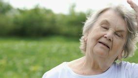 Η χαμογελώντας ώριμη ηλικιωμένη γυναίκα ισιώνει την τρίχα σας απόθεμα βίντεο