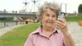 Η χαμογελώντας ώριμη ηλικιωμένη γυναίκα παρουσιάζει ασημένιο έξυπνο τηλέφωνο απόθεμα βίντεο