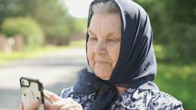 Η χαμογελώντας ώριμη ηλικιωμένη γυναίκα παρουσιάζει smartphone υπαίθρια απόθεμα βίντεο