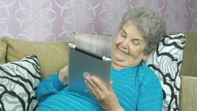 Η χαμογελώντας ανώτερη γυναίκα βρίσκεται επάνω στον καναπέ δωματίου ξενοδοχείου απόθεμα βίντεο