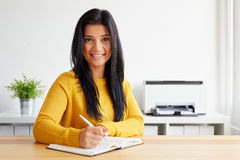 Η χαμογελώντας γυναίκα γράφει τις σημειώσεις Στοκ εικόνα με δικαίωμα ελεύθερης χρήσης