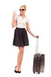 Η χαμογελώντας γυναίκα με τη μαύρη βαλίτσα κάνει το ΕΝΤΑΞΕΙ σημάδι. Στοκ Φωτογραφίες