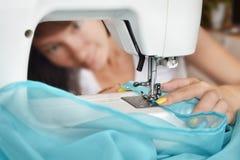 Η χαμογελώντας γυναίκα μοδιστρών ράβει τα ενδύματα στη ράβοντας μηχανή Seamstress και αυτή στενός επάνω χεριών Στοκ Φωτογραφία