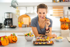Η χαμογελώντας γυναίκα που τρώει το τέχνασμα ή μεταχειρίζεται την καραμέλα αποκριών Στοκ φωτογραφία με δικαίωμα ελεύθερης χρήσης