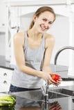 Η χαμογελώντας γυναίκα πλένει τη Apple Στοκ φωτογραφία με δικαίωμα ελεύθερης χρήσης