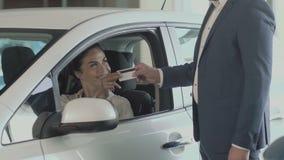 Η χαμογελώντας επιχειρηματίας δίνει μια πιστωτική κάρτα στον πωλητή στη εμπορία αυτοκινήτων φιλμ μικρού μήκους