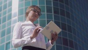 Η χαμογελώντας επιχειρησιακή γυναίκα που φορά τα γυαλιά εργάζεται στην ταμπλέτα της απόθεμα βίντεο
