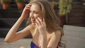 Η χαμογελώντας ελκυστική νέα κυρία στο μοντέρνο μαγιό μιλά στο smartphone απόθεμα βίντεο