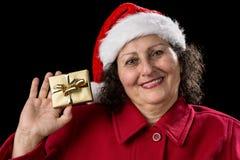 Η χαμογελώντας ηλικιωμένη κυρία παρουσιάζει χρυσό τυλιγμένο δώρο Χριστουγέννων στοκ εικόνα με δικαίωμα ελεύθερης χρήσης