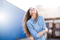 Η χαμογελώντας και ευτυχής νέα γυναίκα εξετάζει μια πλευρά με τη σγουρή τρίχα Στοκ Εικόνες