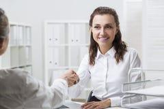 Η χαμογελώντας καφετιά μαλλιαρή γυναίκα τινάζει τα χέρια Στοκ Φωτογραφία