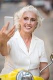 Η χαμογελώντας κυρία εξετάζει το τηλέφωνο Στοκ φωτογραφία με δικαίωμα ελεύθερης χρήσης