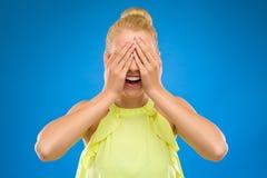 Η χαμογελώντας νέα γυναίκα κλείνει τα μάτια της με τα χέρια. Στοκ Εικόνα