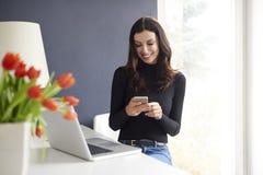 Η χαμογελώντας νέα γυναίκα στέλνει το μήνυμα Στοκ Εικόνα