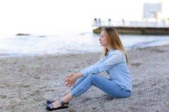 Η χαμογελώντας νέα γυναίκα στηρίζεται στην παραλία και θέτει κεκλεισμένων των θυρών, κάθισμα Στοκ εικόνες με δικαίωμα ελεύθερης χρήσης