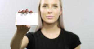 Η χαμογελώντας νέα ξανθή γυναίκα παρουσιάζει επαγγελματική κάρτα απόθεμα βίντεο