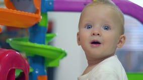 Η χαρά συγκινήσεων χαριτωμένου λίγο παιδί στο δωμάτιο παιχνιδιών επάνω το υπόβαθρο απόθεμα βίντεο