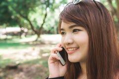 Η χαριτωμένη ασιατική γυναίκα μιλά στο κινητό τηλέφωνο καθμένος στο πάρκο στη θερμή ημέρα άνοιξη Στοκ Φωτογραφίες