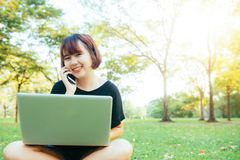 Η χαριτωμένη ασιατική γυναίκα χαμογελά και μιλώντας στο κινητό τηλέφωνο καθμένος στην ημέρα άνοιξη πάρκων Στοκ φωτογραφίες με δικαίωμα ελεύθερης χρήσης