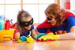 Η χαριτωμένη γυναίκα και η κόρη παιδιών της έντυσαν όπως τα superheroes που καθαρίζουν το πάτωμα και το χαμόγελο Στοκ Εικόνες