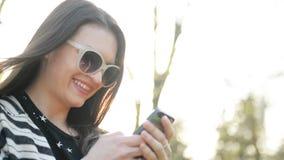 Η χαριτωμένη γυναίκα με τα γυαλιά ηλίου και μακρυμάλλης χρησιμοποιεί την κινητή συσκευή απολαμβάνοντας τις ηλιαχτίδες και τη θερμ απόθεμα βίντεο