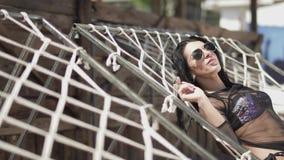 Η χαριτωμένη γυναίκα στο ασημένιο κοστούμι swimmimg κάνει ηλιοθεραπεία την τοποθέτηση στο κρεβάτι σχοινιών Ελεύθερος χρόνος της χ απόθεμα βίντεο