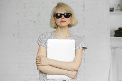 Η χαριτωμένη γυναίκα hipster φορά τα γυαλιά ηλίου και κρατά το lap-top στο φως της ημέρας Στοκ εικόνα με δικαίωμα ελεύθερης χρήσης