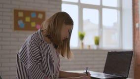 Η χαριτωμένη ελκυστική μαθήτρια ακούει προσεκτικά το δάσκαλο και γράφει με το αριστερό χέρι της 4K φιλμ μικρού μήκους