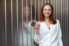Η χαριτωμένη επιχειρηματίας περιμένει την κλήση, κρατά το σύγχρονο τηλέφωνο κυττάρων, που ντύνεται στον άσπρο άλτη, συνδέει την κ στοκ εικόνες