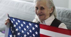 Η χαριτωμένη ηλικιωμένη γυναίκα με τις ρυτίδες κάθεται στον καναπέ και κρατά τη αμερικανική σημαία στο σπίτι απόθεμα βίντεο