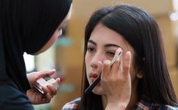 η χαριτωμένη διασκέδαση καλλυντικών που έχει κάνει makeup τα προϊόντα επάνω στη γυναίκα Στοκ Φωτογραφίες