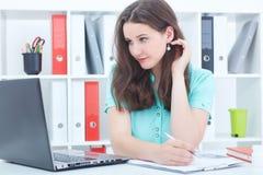 Η χαριτωμένη καυκάσια επιχειρηματίας στο τηλέφωνο που γράφει κάτι κάτω εξετάζει την οθόνη στο γραφείο της Στοκ Εικόνες