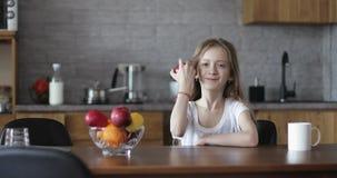 Η χαριτωμένη μαθήτρια κάθεται στον πίνακα και παρουσιάζει όμορφο κόκκινο μήλο απόθεμα βίντεο
