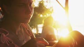 Η χαριτωμένη νέα γυναίκα κάθεται στο μόνιππο -μόνιππο-longue, τρώει το καρπούζι και την πίτσα στο ηλιοβασίλεμα απόθεμα βίντεο