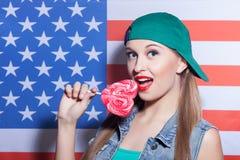 Η χαριτωμένη νέα γυναίκα δοκιμάζει τη γλυκιά καραμέλα στοκ φωτογραφίες