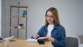 Η χαριτωμένη νέα γυναίκα που βάζει το έξυπνο τηλέφωνο στον πίνακα και αρχίζει στο σημειωματάριο στο σπίτι απόθεμα βίντεο