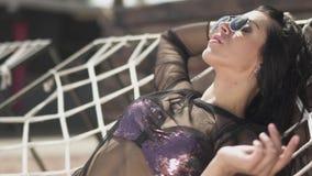 Η χαριτωμένη νέα γυναίκα στο ασημένιο κοστούμι swimmimg κάνει ηλιοθεραπεία την τοποθέτηση στο κρεβάτι σχοινιών Ελεύθερος χρόνος τ απόθεμα βίντεο