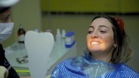 Η χαριτωμένη νέα γυναίκα brunette κινηματογραφήσεων σε πρώτο πλάνο κάθεται στην οδοντική καρέκλα και κρατά τον καθρέφτη μπροστά α φιλμ μικρού μήκους
