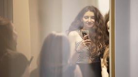Η χαριτωμένη νέα γυναίκα brunette στέκεται σε κάποιο γεγονός στα συμπαθητικά ενδύματα απόθεμα βίντεο