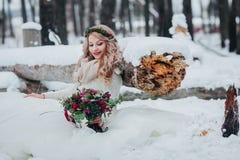 Η χαριτωμένη νύφη κάθεται στο χιόνι πλησίον στο ξύλινο κούτσουρο και κρατά μια ανθοδέσμη γαμήλιος χειμώνας νεόνυμφων νυφών υπαίθρ Στοκ Εικόνα