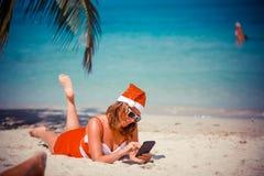 Η χαριτωμένη ξανθή γυναίκα στο κόκκινα φόρεμα, τα γυαλιά ηλίου και το καπέλο santa που βρίσκεται στην εξωτική τροπική παραλία στο Στοκ Φωτογραφίες
