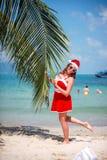 Η χαριτωμένη ξανθή γυναίκα στο κόκκινα φόρεμα, τα γυαλιά ηλίου και το καπέλο santa στέκεται στο φοίνικα στην εξωτική τροπική παρα Στοκ Φωτογραφίες