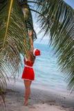 Η χαριτωμένη ξανθή γυναίκα στο κόκκινο καπέλο φορεμάτων και santa πηδά στην καρύδα φοινίκων στην εξωτική τροπική παραλία Έννοια δ Στοκ Φωτογραφία
