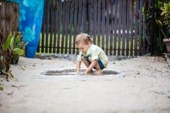 Η χαριτωμένη ξυπόλυτη βύθιση αγοριών παραδίδει τη λακκούβα Στοκ Εικόνα